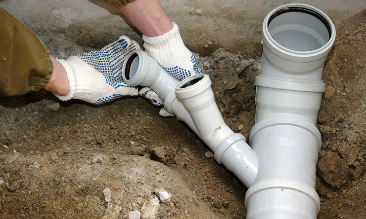 Hands with work gloves turning a sewer pipe